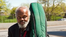 Henry Grimes, outside, holds a double bass in a green, material bag