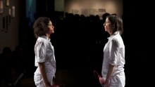 Two women face each other, wearing white boilersuits, and splattered with blood