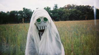 A figure in white cloth whose face wears a mask with green eye is in a field