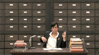 An actor playing a reporter at a trial sits in front of a drawered wall