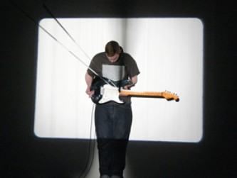 Benedict Drew stands and plays a guitar in front of a white and black screen