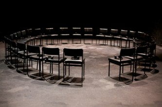 A performance space set up with a ring of black chairs, all facing inwards