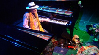 Charlemagne Palestine in a white hat playing two pianos