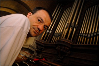 Jean-Luc Guionnet sits to the left of a set of large organ pipes