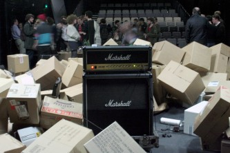 A Marchall stack, a lot of cardboard boxes and an audience in the background