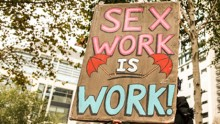 a banner with painted letters saying sex work is work