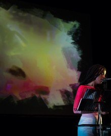 Juliana Huxtable speaks into a mic at a music stand, a blurry film behind