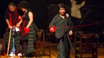 Figures in dark costumes spool red thread across a stage