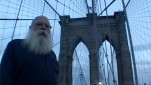 Samuel Delany looks down at camera as the brooklyn bridge looms behind him