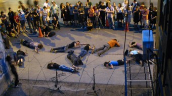 Performers lie on the floor face-down, hitting a microphone against the concrete