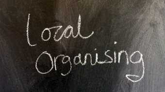 A chalkboard with the words Local Organising written in white chalk