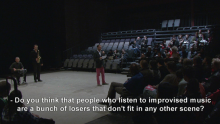 A video screen grab of a man addressing an audience about improvised music