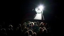 A view of a dark room and an audience from behind.A huge backlit fan is on stage